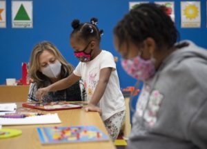 Aimee Dunn, left, who owns Clubhouse Kids with her husband Chris Dunn, works with the newly-opened childcare center's first two enrollees Monday. Staff photo by Graham Cullen